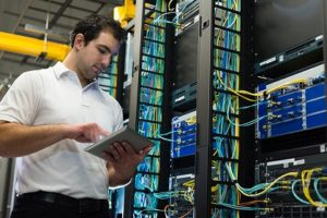 Network technician working in a datacenter or server room